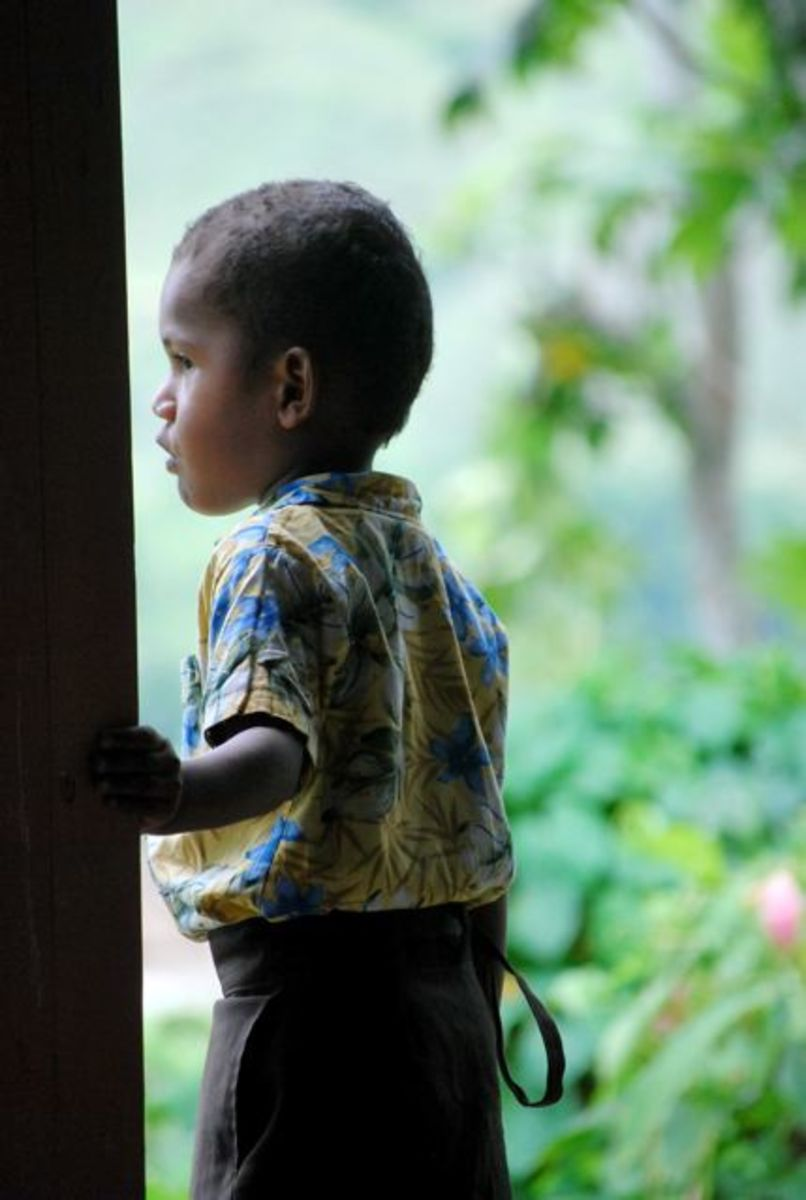 Fijian boy looks out the doorway