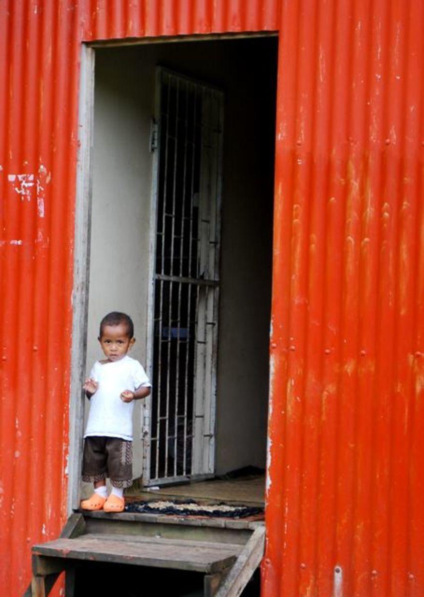 A Fijian boy stands in a doorway