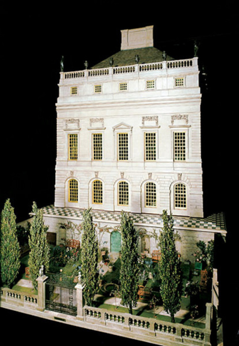 The front facade of queen Mary's Dollhouse, complete with cypress trees and a garden