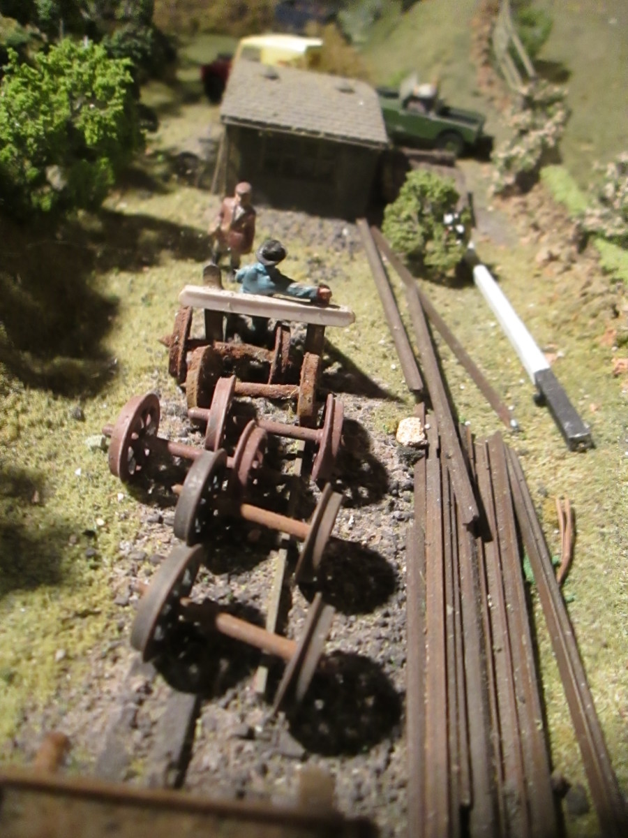 Assorted lineside detritus, plastic axles and wheels painted to resemble rusted steel. At the back is a pair of Ratio sheds fixed together,  painted and weathered to look like creosoted timber