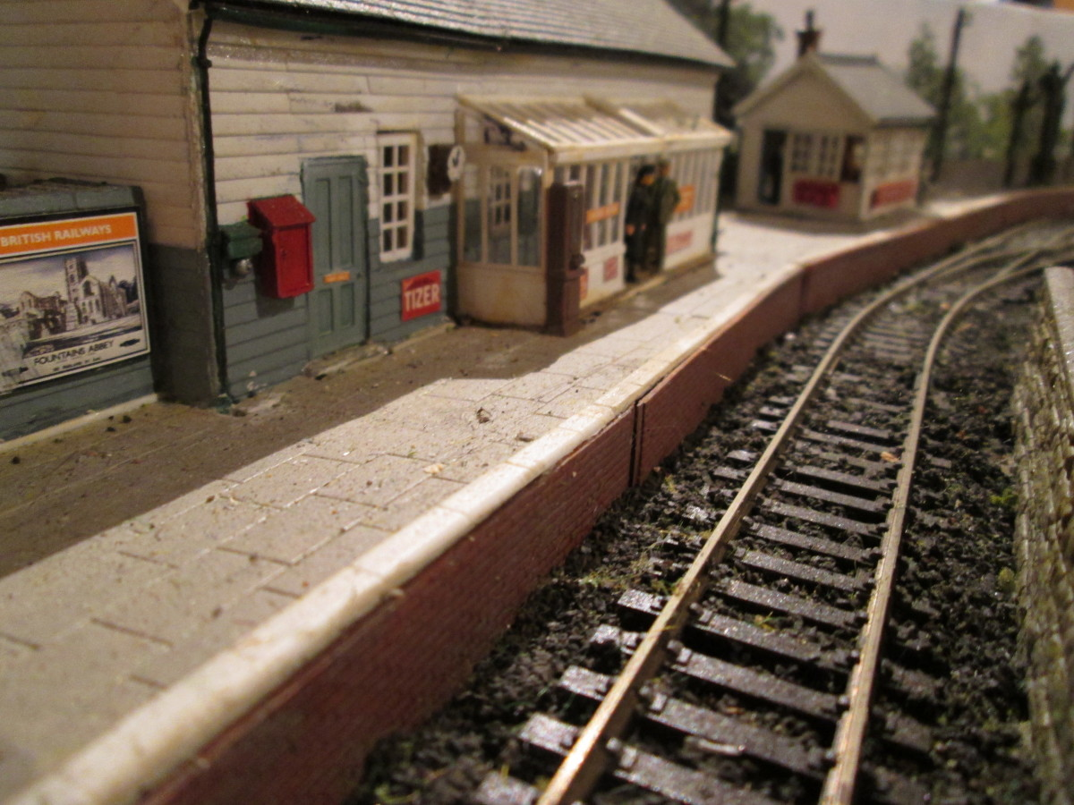 The view along the platform to the Ratio signal cabin (minus lamp room and steps). Platform is Wills' Victoria Stone, track is Peco Setrack and Streamline - travel poster from Trackside Signs