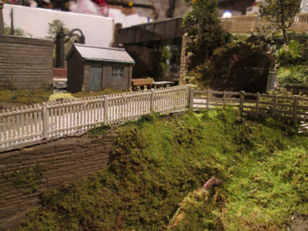Part of the 'carr' (marsh) beside the coal depot inclined road; two modified plastic yard building kits make up the scene. Coarse stone wall below the road is Wills', of course.