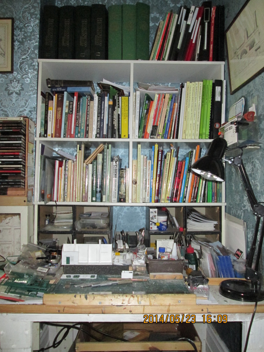 The work area. Reference 'Library' above (bound magazines, paperbacks, preservation info, NYMR and WR share certificates). Other books below, tools & materials, cutting board etc