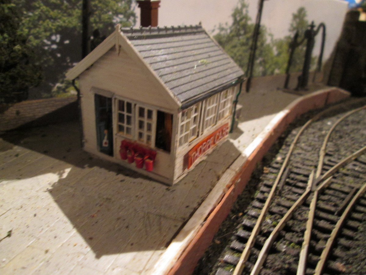 Signal cabin with open door and porter leaning in (lamp in hand) to speak to the 'bobby' ; Wills' (signalman); Interior detailing added. Wills' dressed stone wall (behind) and brick platform facing on pine framework; Mike's Models NER water crane