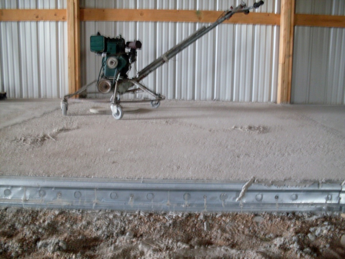 A machine to smooth the leveled underlayment for the concrete pad sits off to the side, on a section which has already been done.