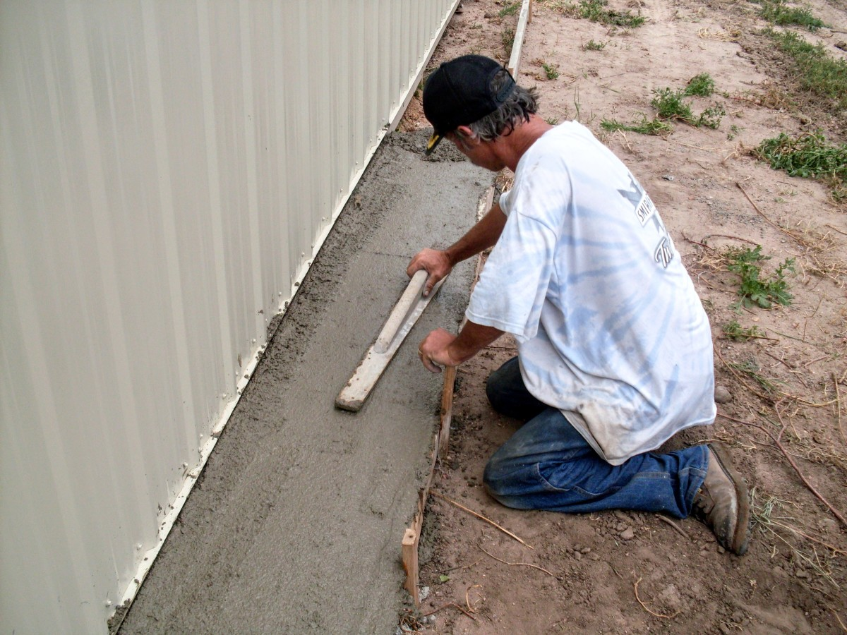 My husband uses a hand-held float to smooth the concrete along the outside wall of the building.
