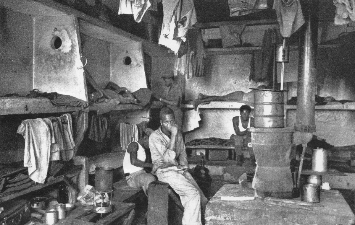 Miners in their crowded and squalid living quarters with more bunks.