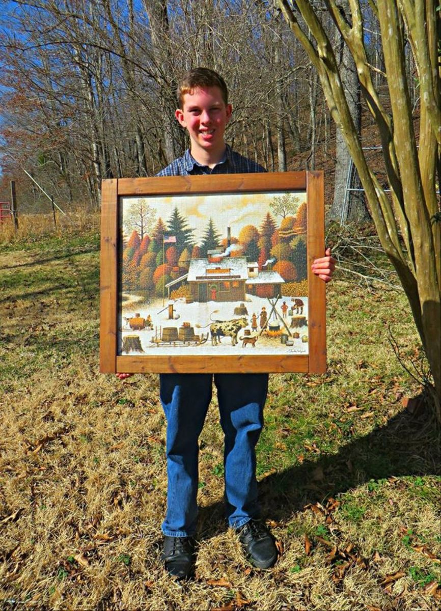 Grantley Waters and his finished and framed primitive folk art puzzle by Charles Wysocki, the Sugar Spigot, from our maples to your tables ... he made the frame himself from wood in the barn, hand sanded and stained, 1000 Piece ...