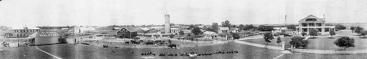 Panoramic view of the 101 ranch showing farm buildings, residences, ranch hands, farm machinery, and animals.