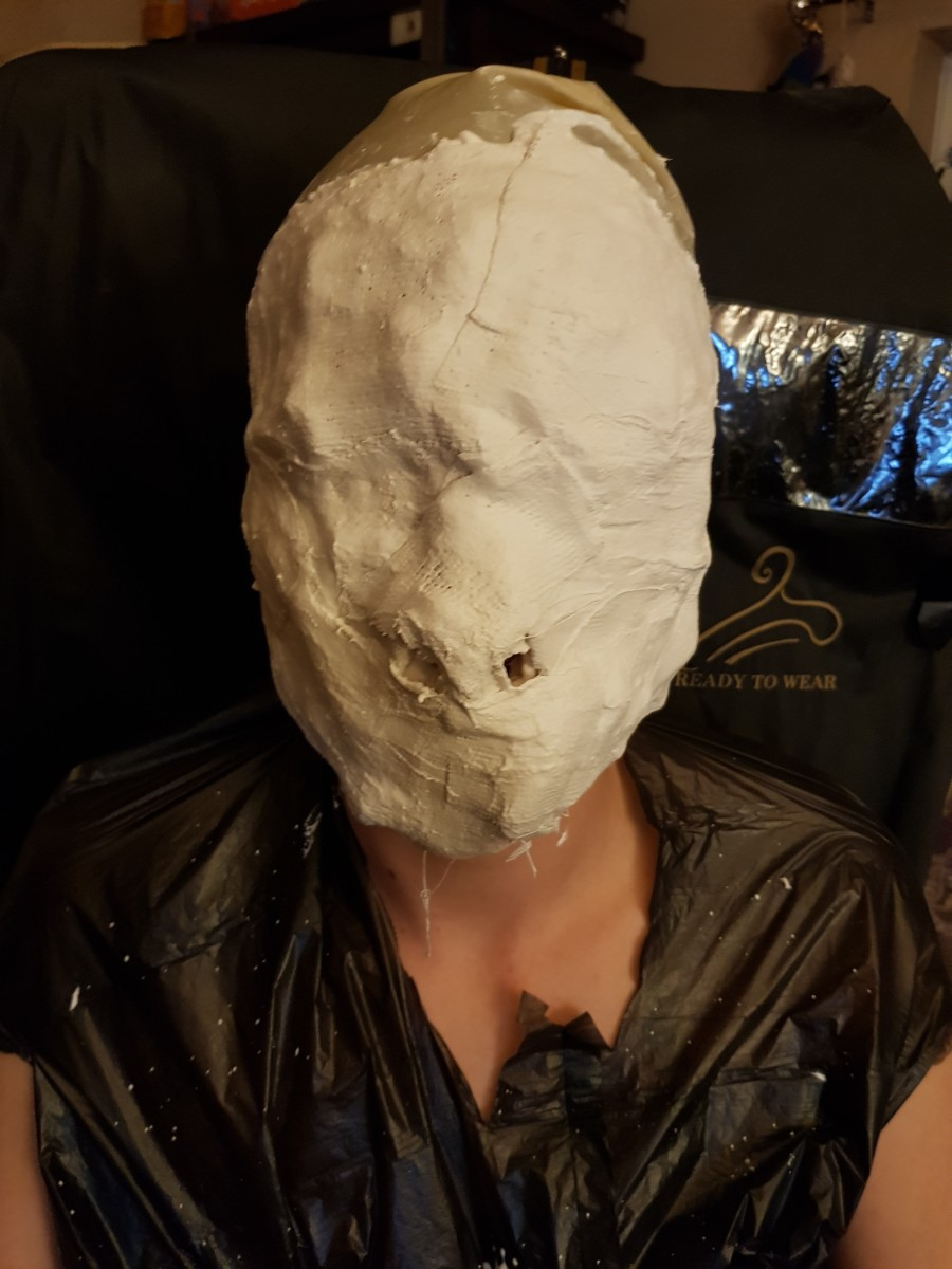 Model with plaster strips on face.