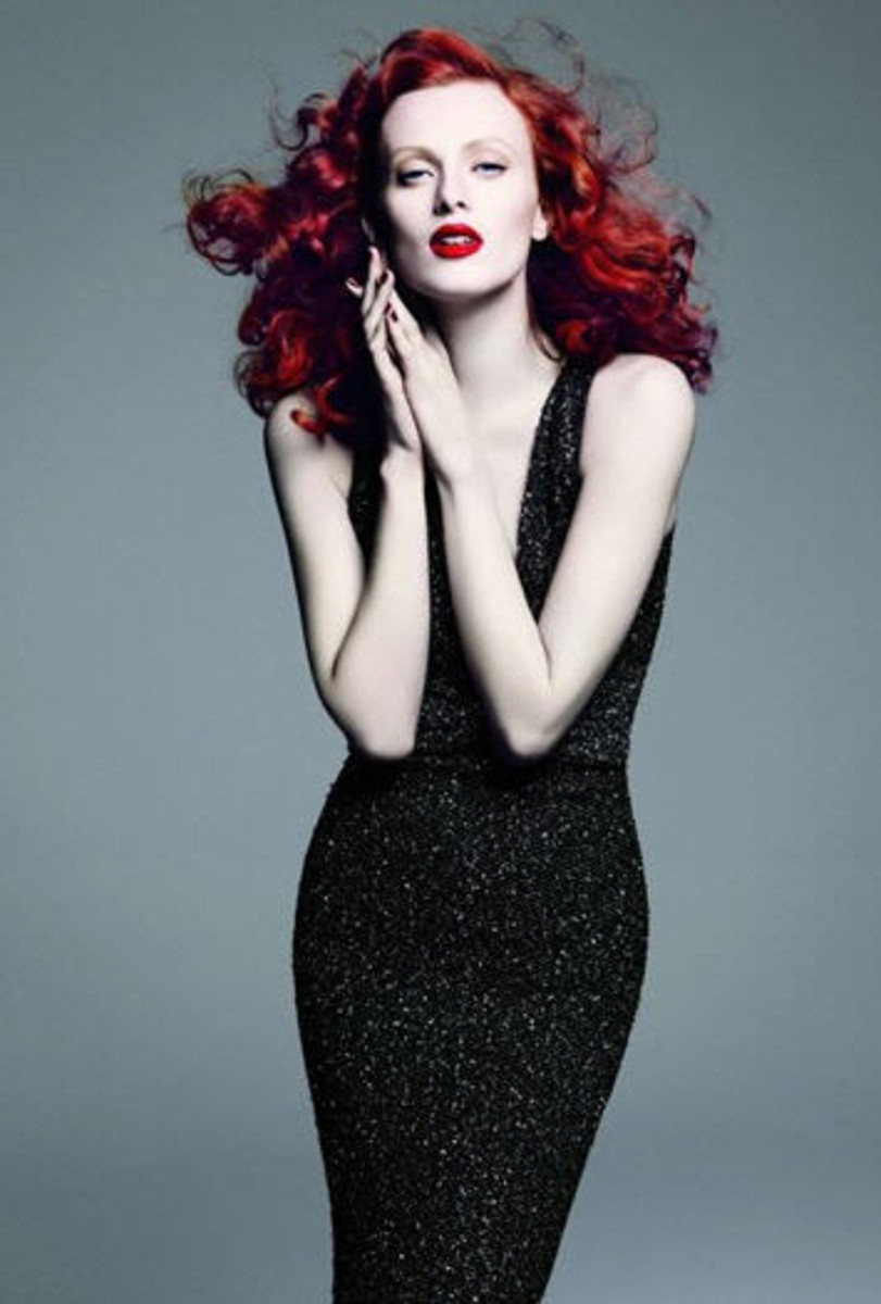 St John advertisement with glamorous red head wearing a black evening gown