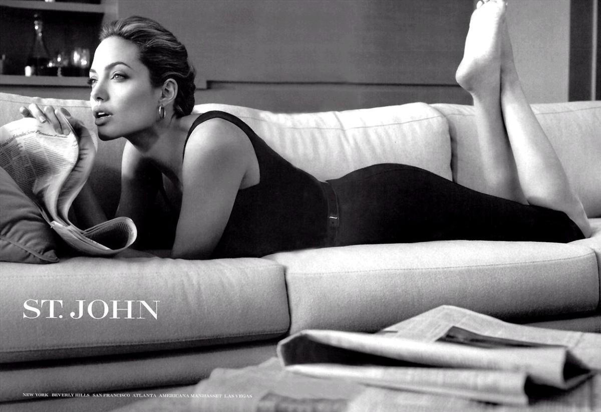 St John black and white advertisement with Angelina Jolie laying prone on a white sofa