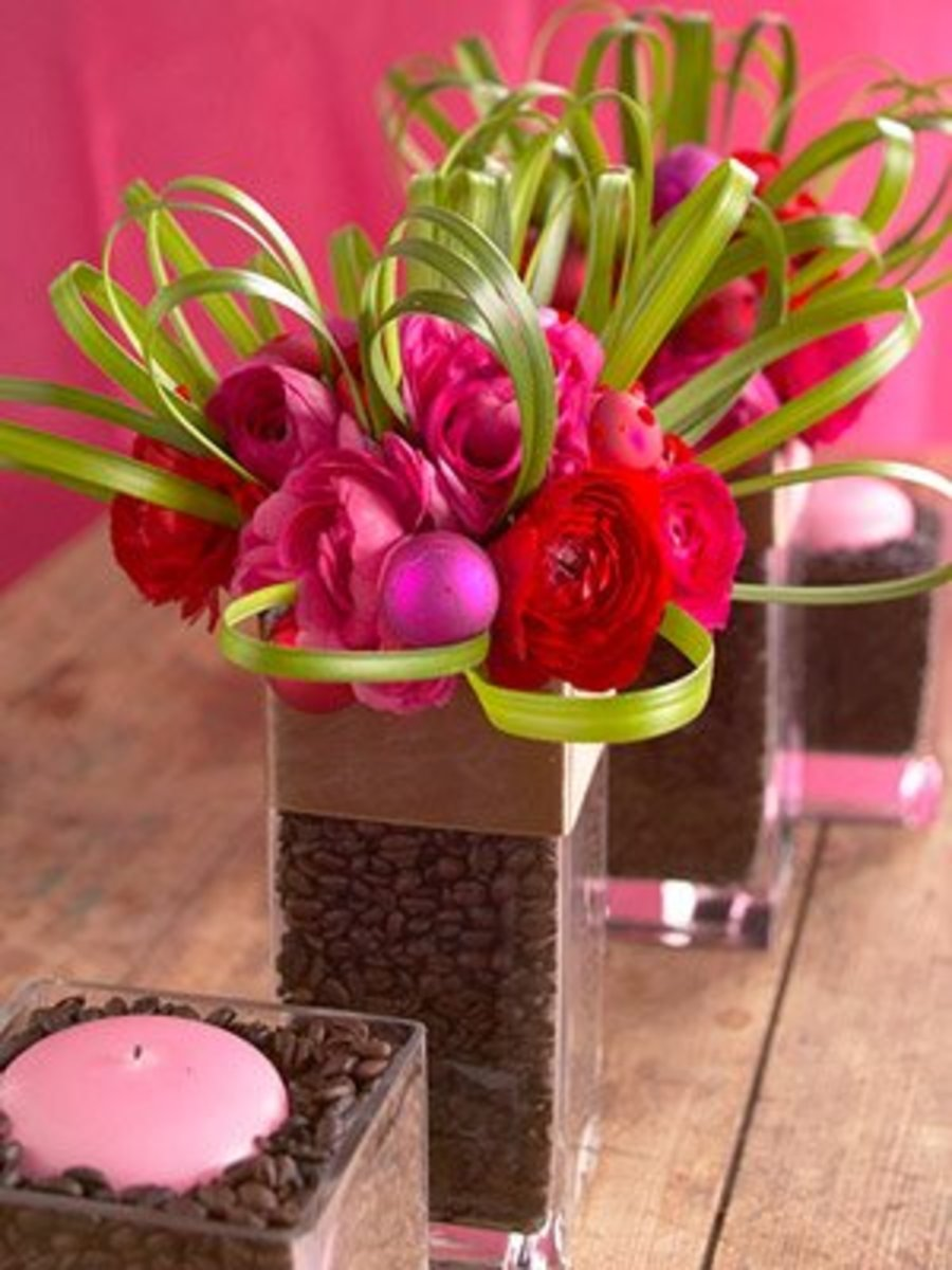 Fuchsia peonies and roses stuck in a clear glass vase filled with coffee beans make a creative and modern centerpiece.