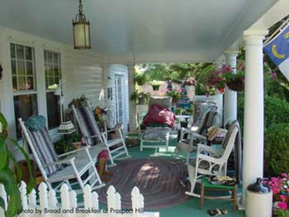 Rocking chairs add to the comfort of this well furnished country style porch.