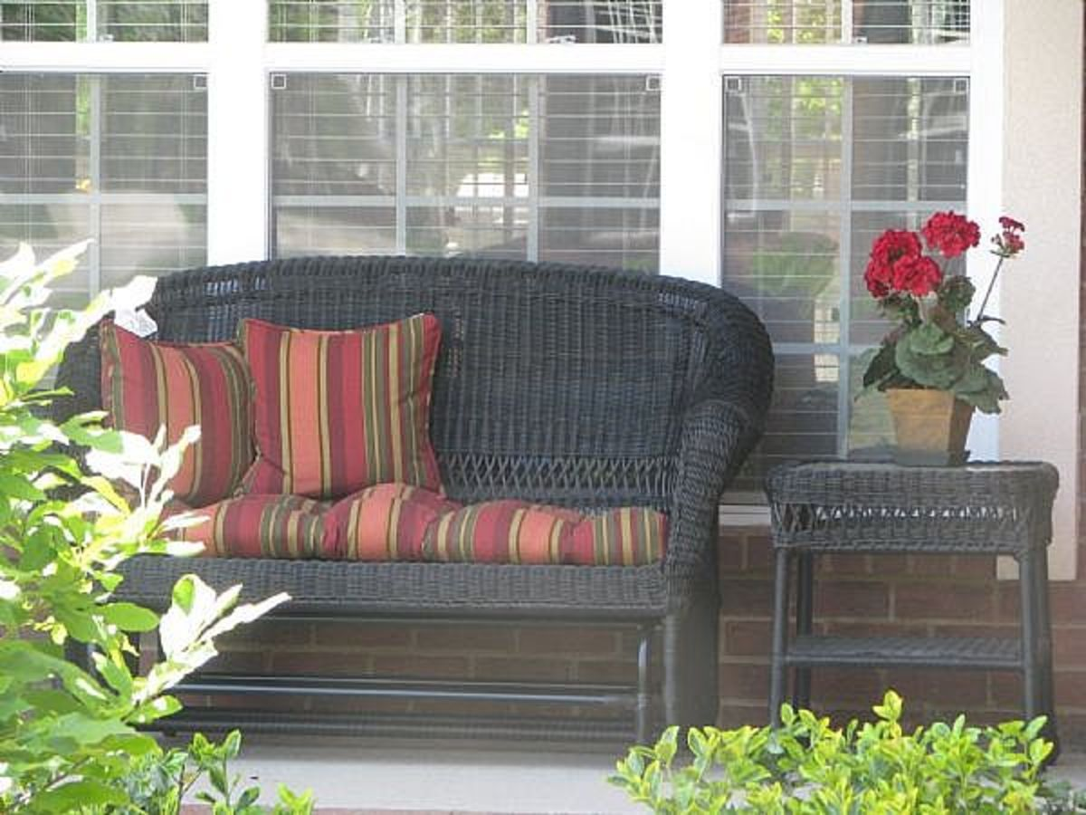 Pillows, flowers, and a wicker table add to the country style look and feel.