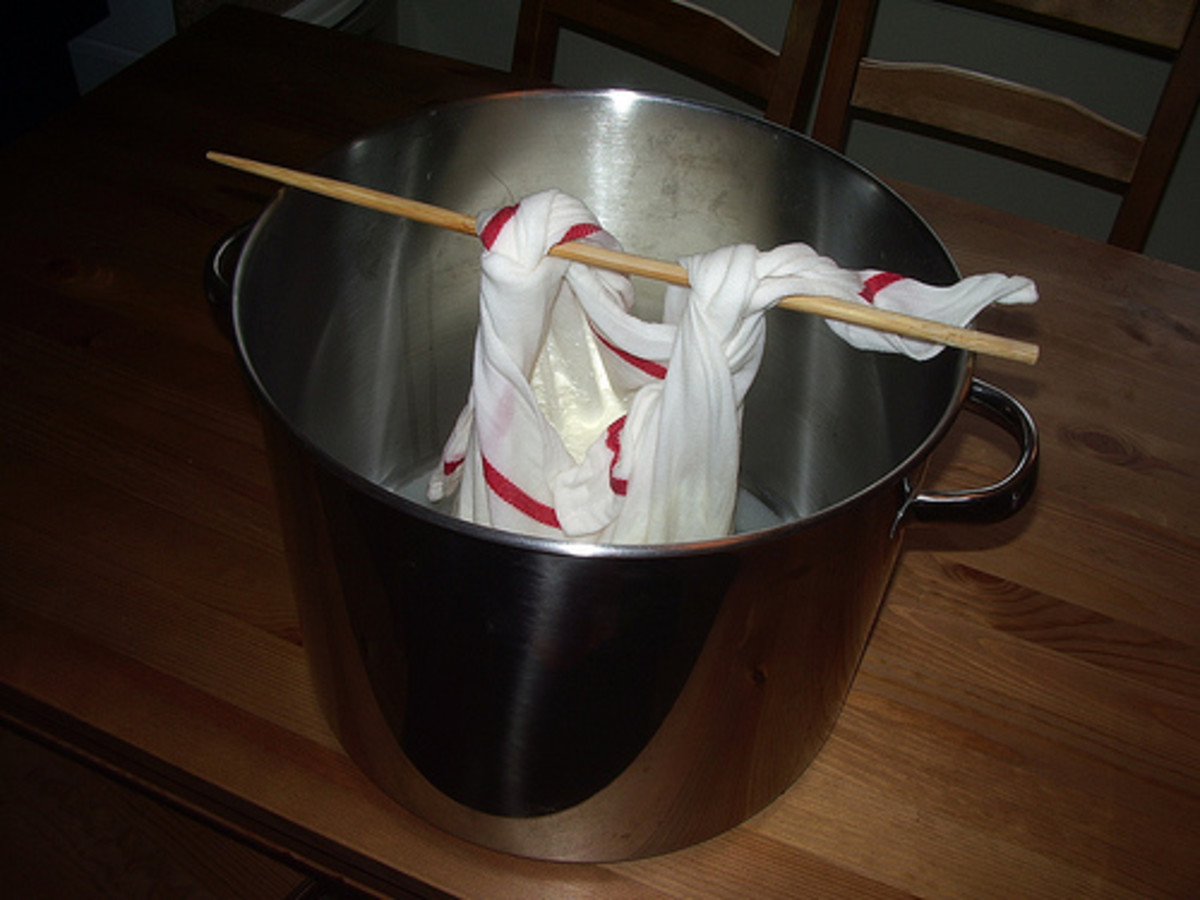 using a chopstick to support curds over milk pot to further drain