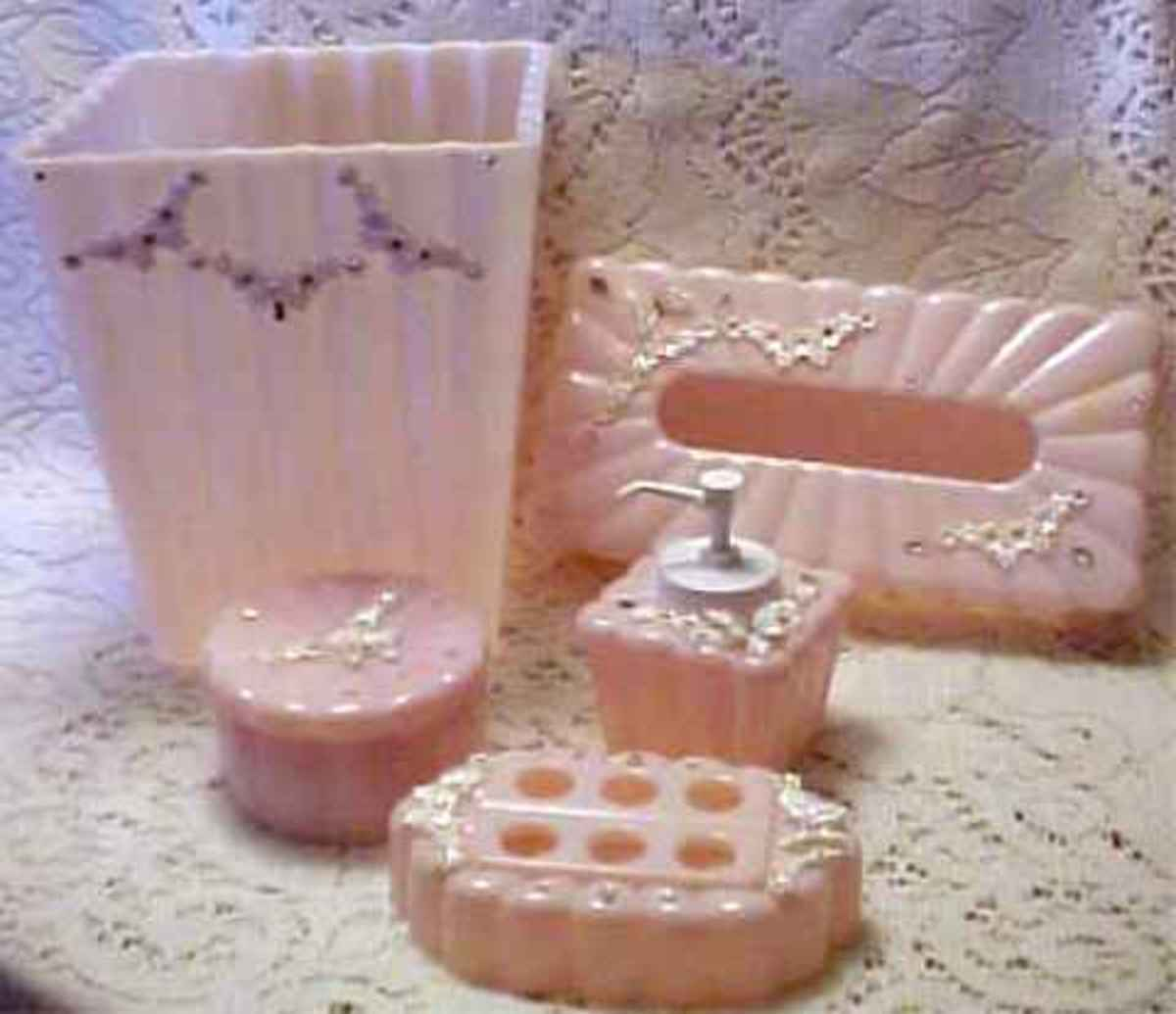 pink bathroom accessories such as toothbrush holder, tissue box, water, perfume and wastebasket