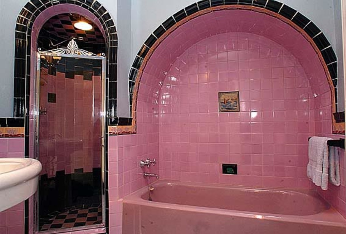 pink bathroom with vintage tile in pink and black with arch around bathtub enclosure