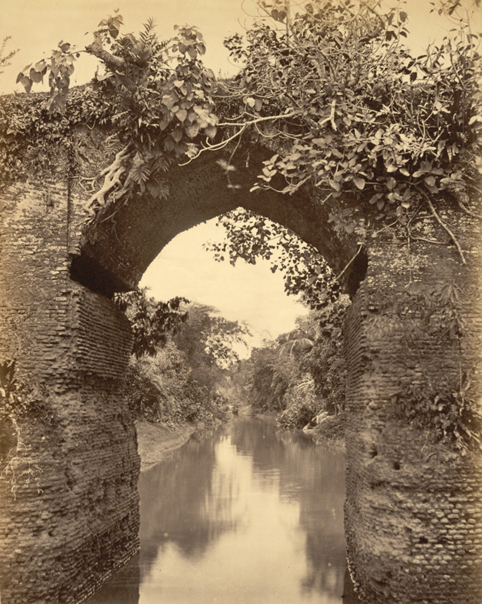 View through the central arch of an ancient bridge over a canal, Sonargaon. 1870