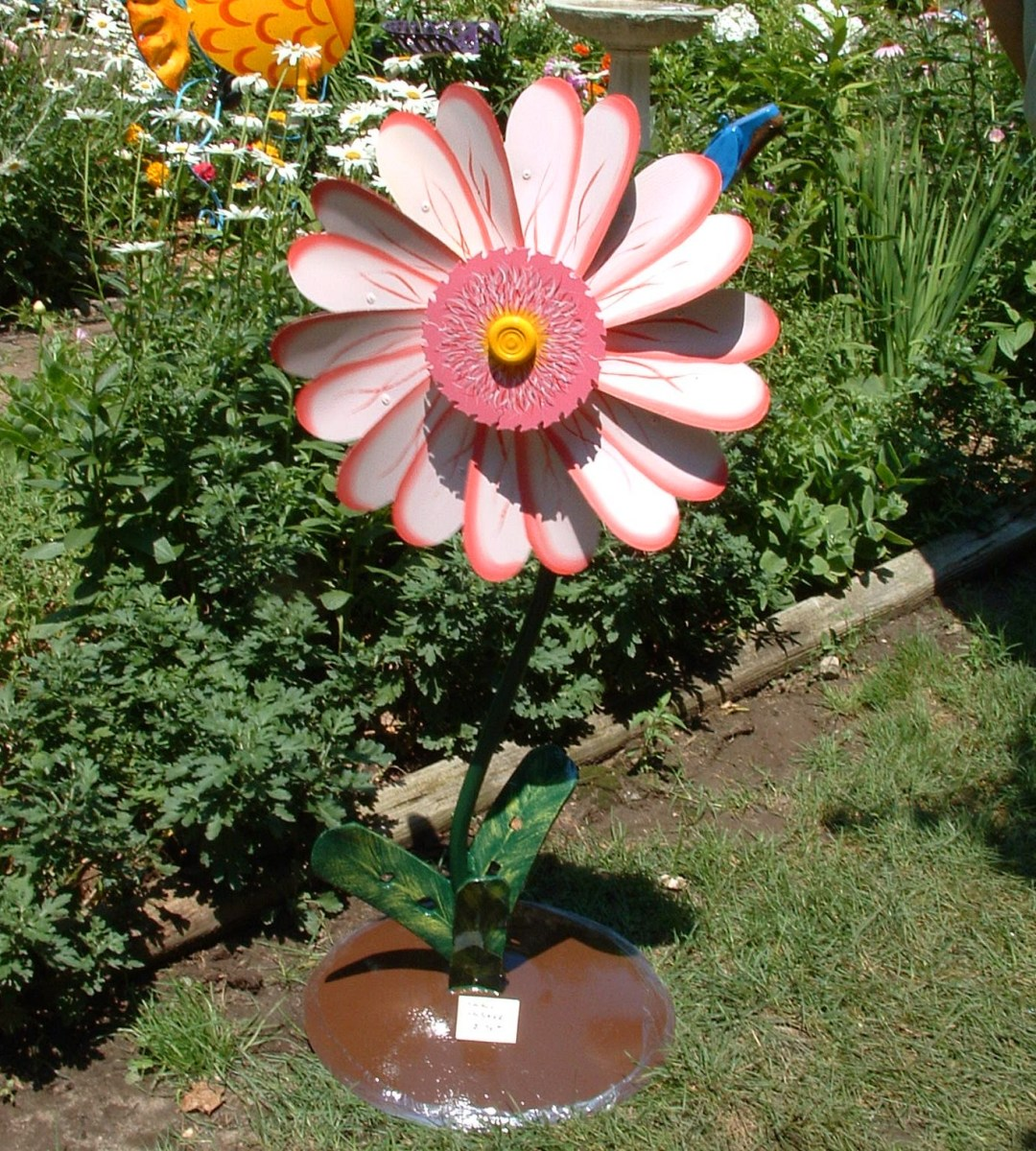 Whimsical spinner flower made out of recycled bicycle wheel. It spins like a pinwheel when the wind blows.