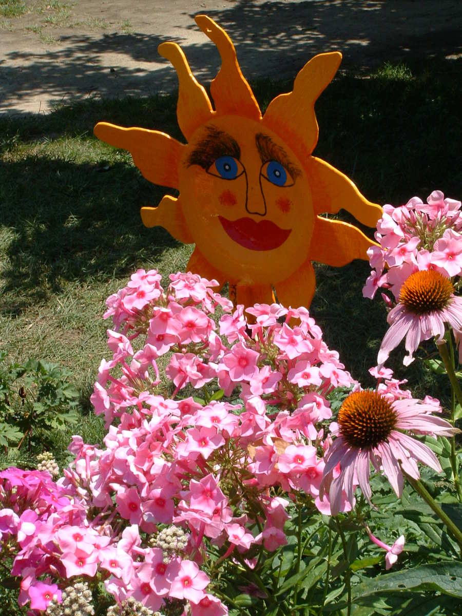 Whimsical metal sunflower tucked in between the garden flowers stays bright and sunny regardless of the weather.