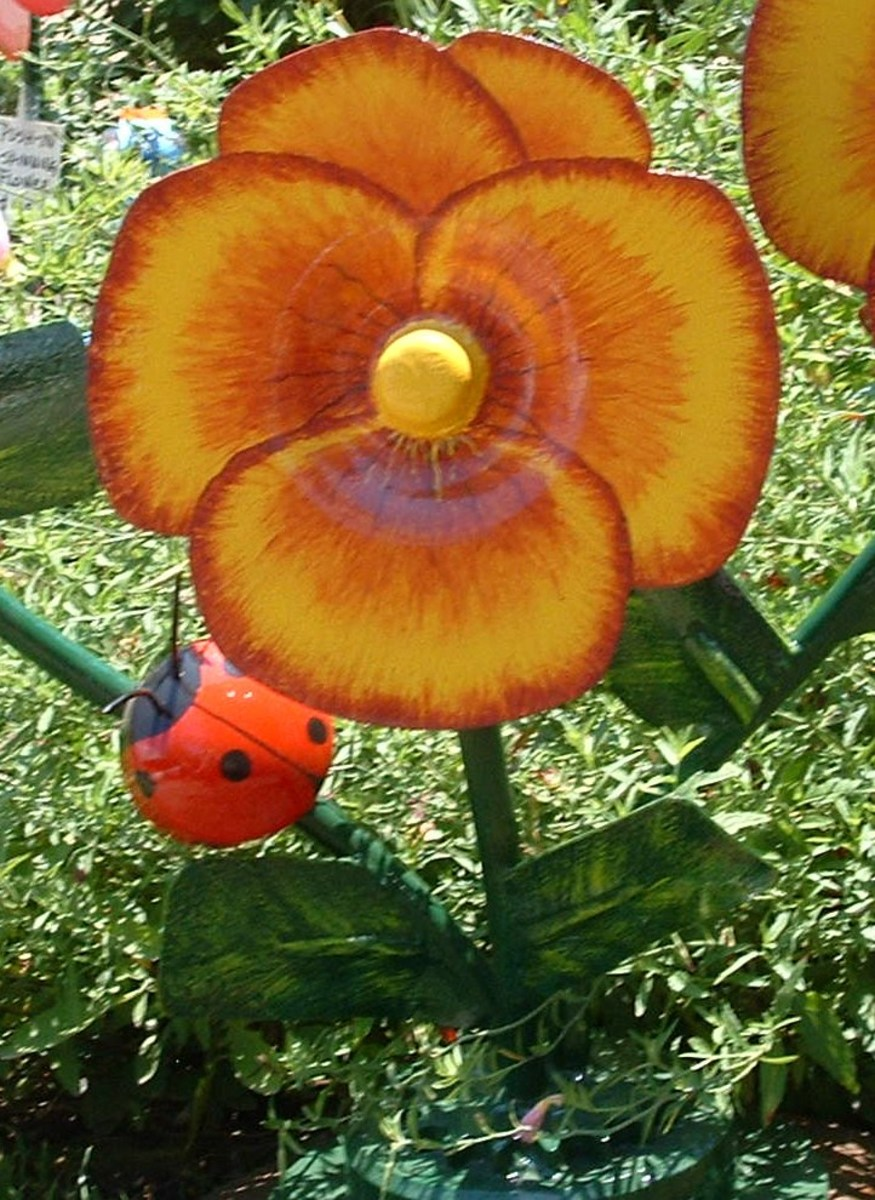 Close up of pansy and ladybug. The sculpture itself has 3 pansies.