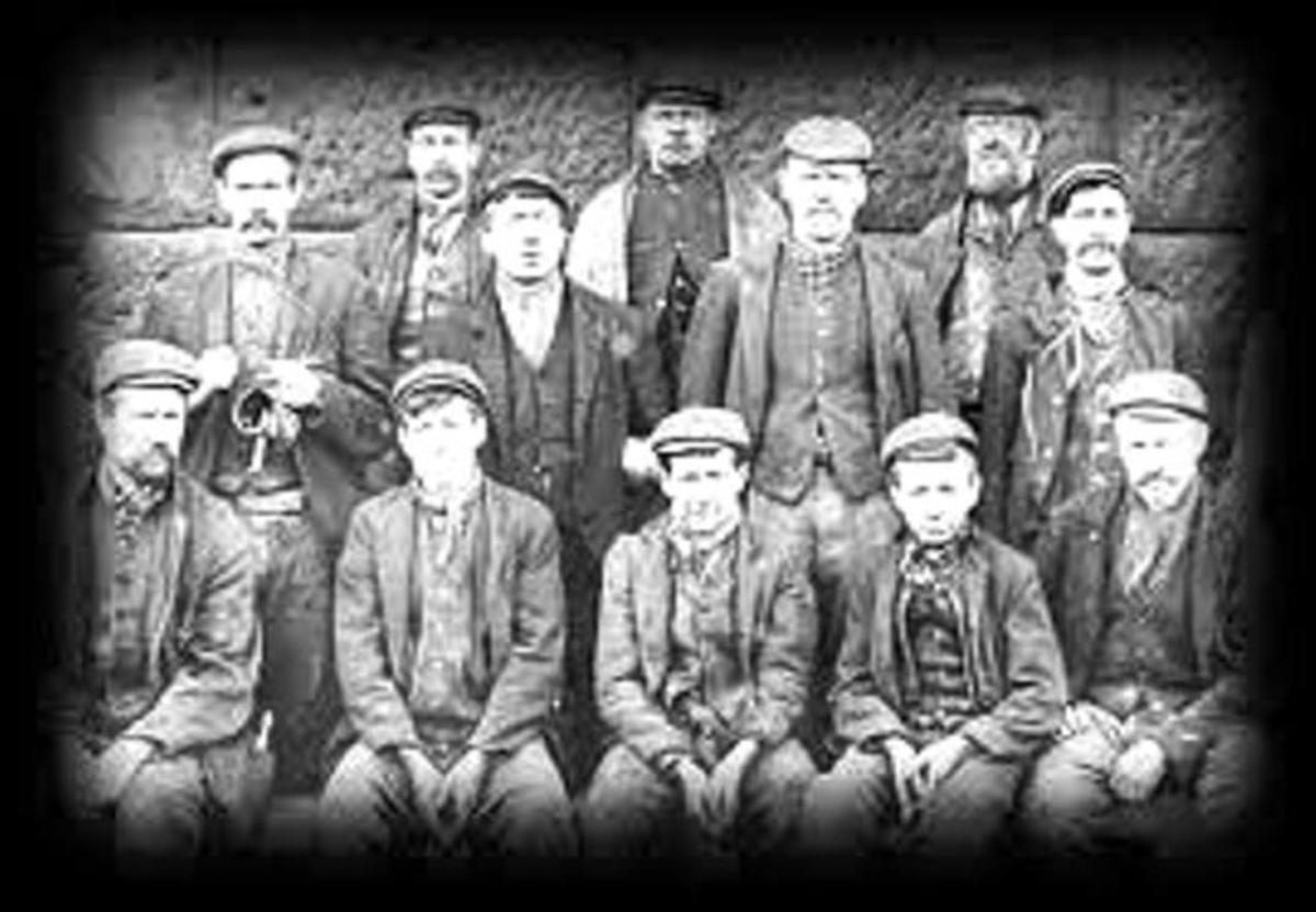 A group photograph taken at Pit Top (Upsall) in front of the steam winder that operated the cage used by the miners to descend into the pit to go to work