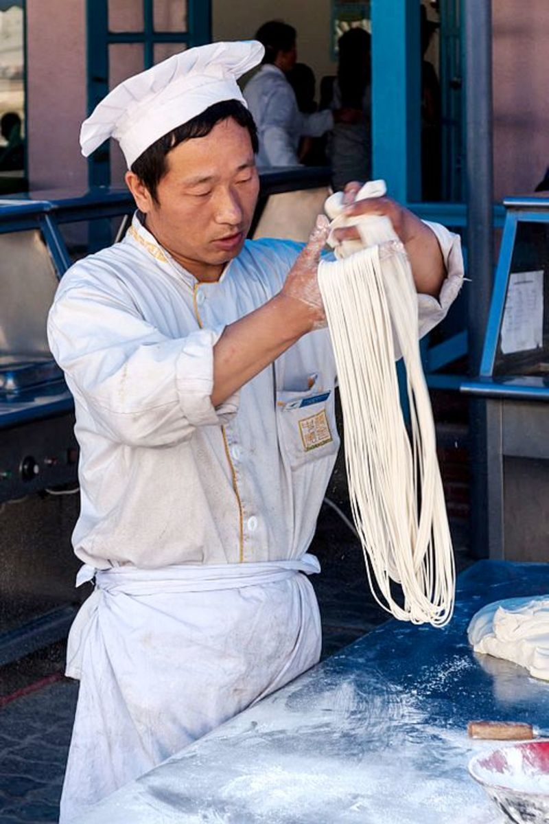 Skilled cook produces long strands of noodles in record time.