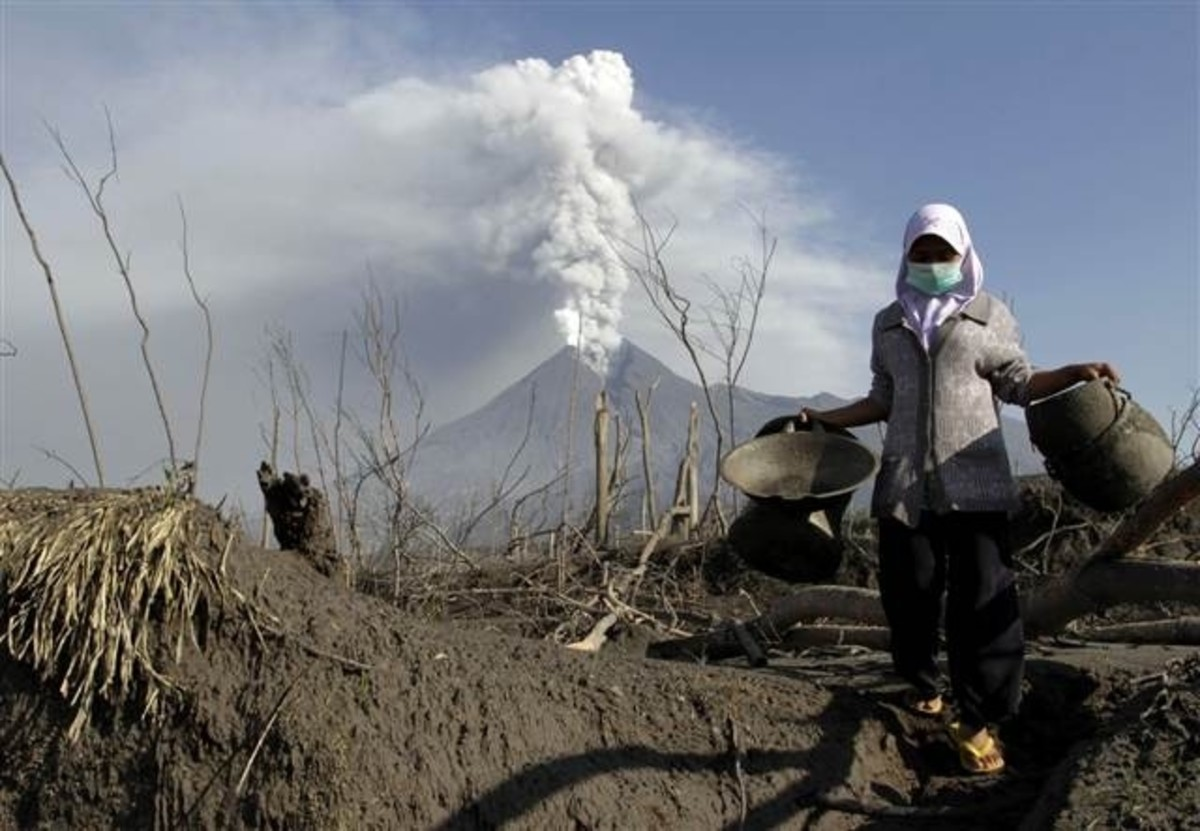 A woman with her face covered walks away from a land volcano that caused a tsunami