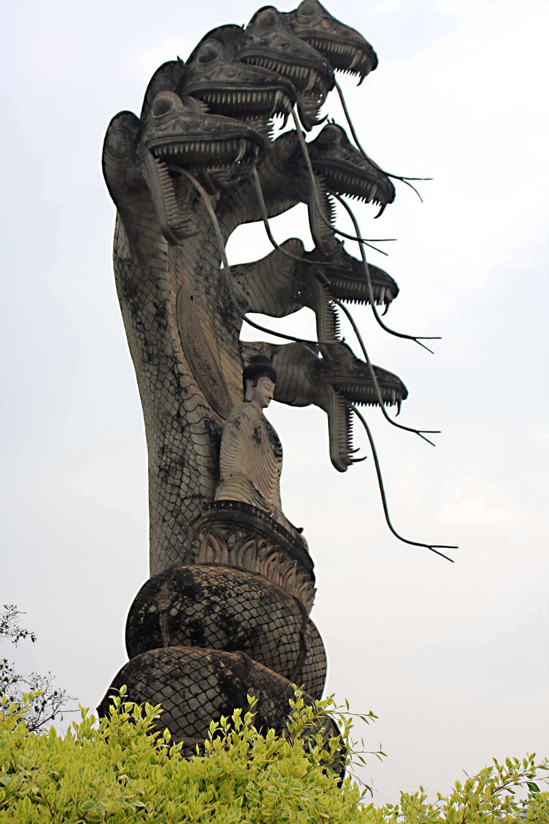 A statue of a seven-headed naga (snake) protecting a meditating Buddha