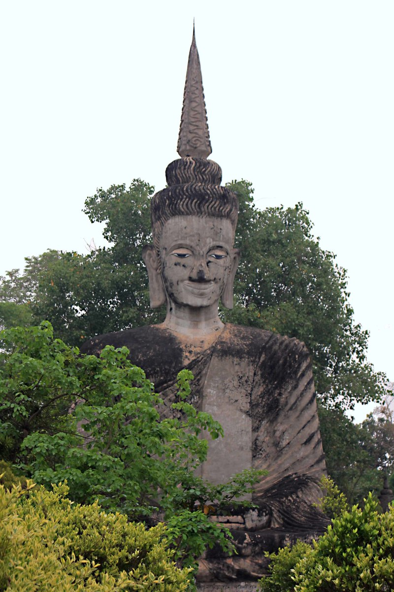 A tall Buddha statue rises serenely above the trees in Salakeoku Park