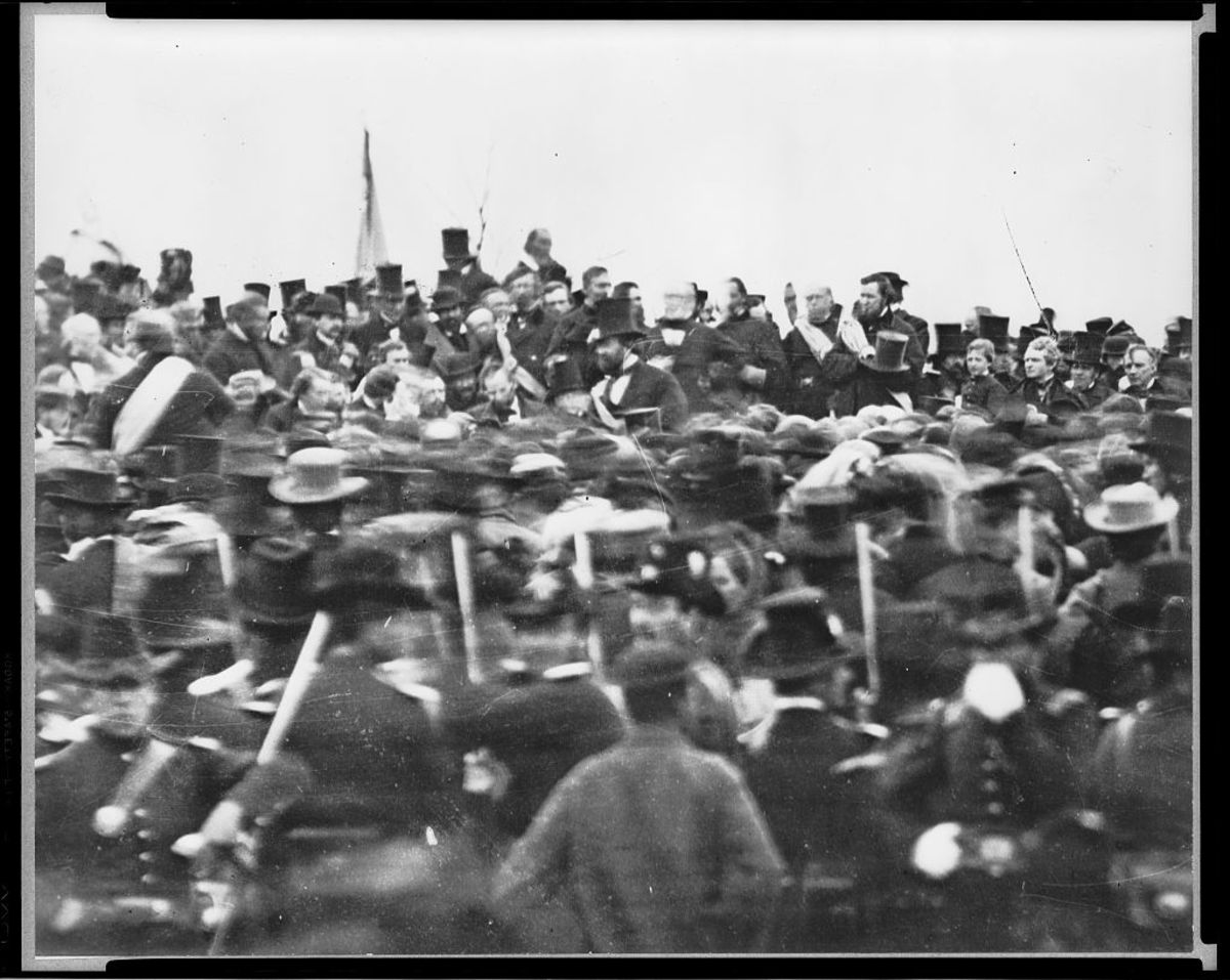 No photos of Lincoln  delivering the address are known to exist.  Photography was in its infancy, and the speech was no doubt over by the time an apparatus could be set up.  This shot shows a rather disorganized group around  the platform.