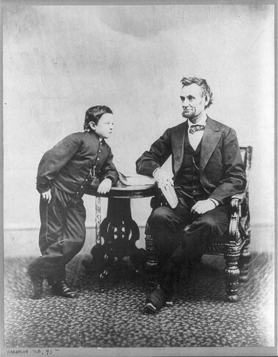 [Abraham Lincoln, seated and holding a book, with his son Tad (Thomas) leaning on a table.