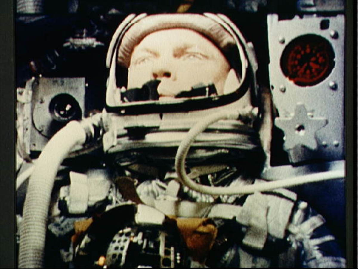Photo of John Glenn taken during Friendship 7 mission shows hoses attached to either side of the helmet, one for venting carbon dioxide, and one to help seal the faceplate when closed. Photo courtesy of NASA.