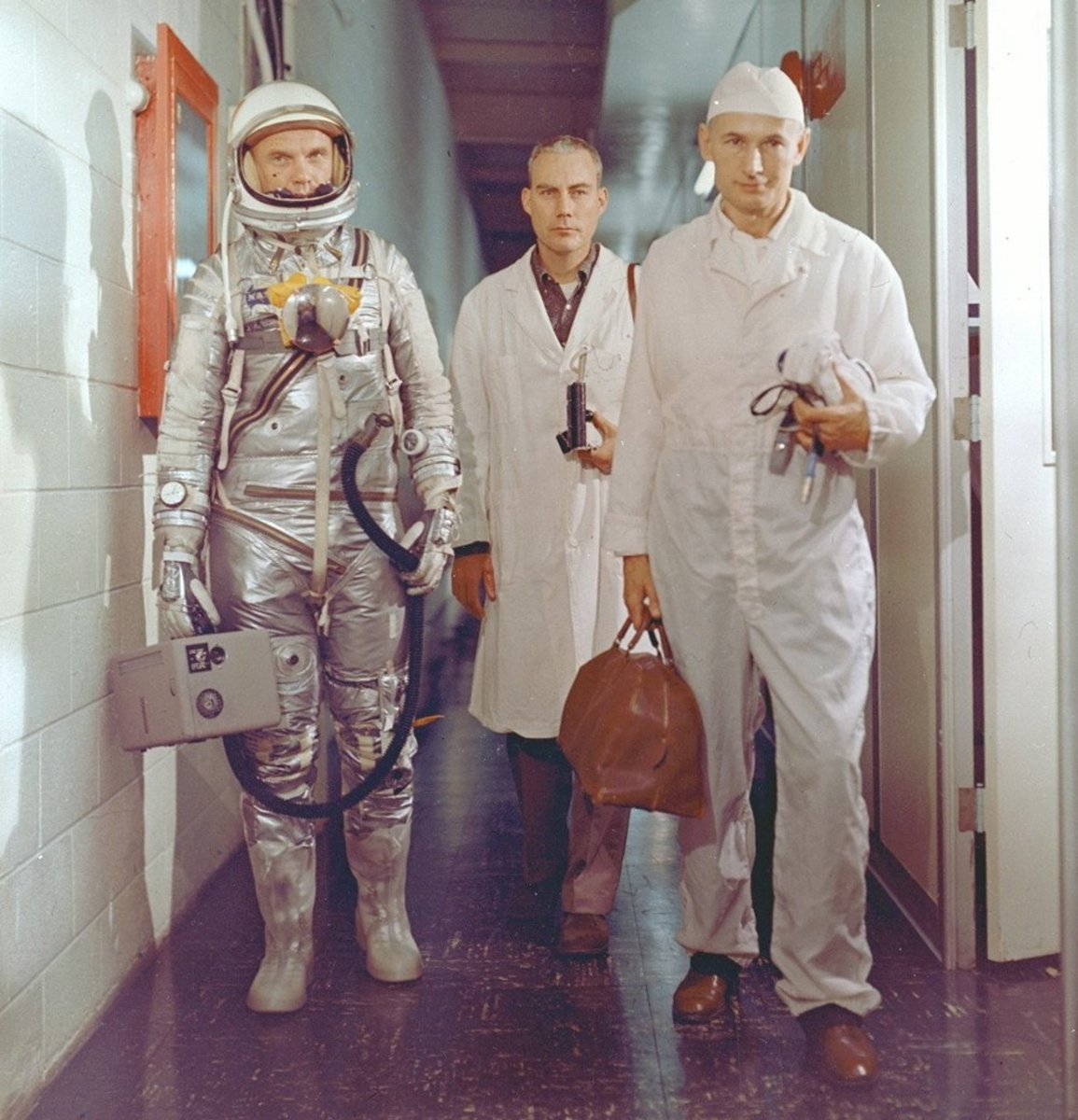 John Glenn, suited-up pre-flight, is seen carrying the portable ventilation unit. Photo courtesy of NASA.