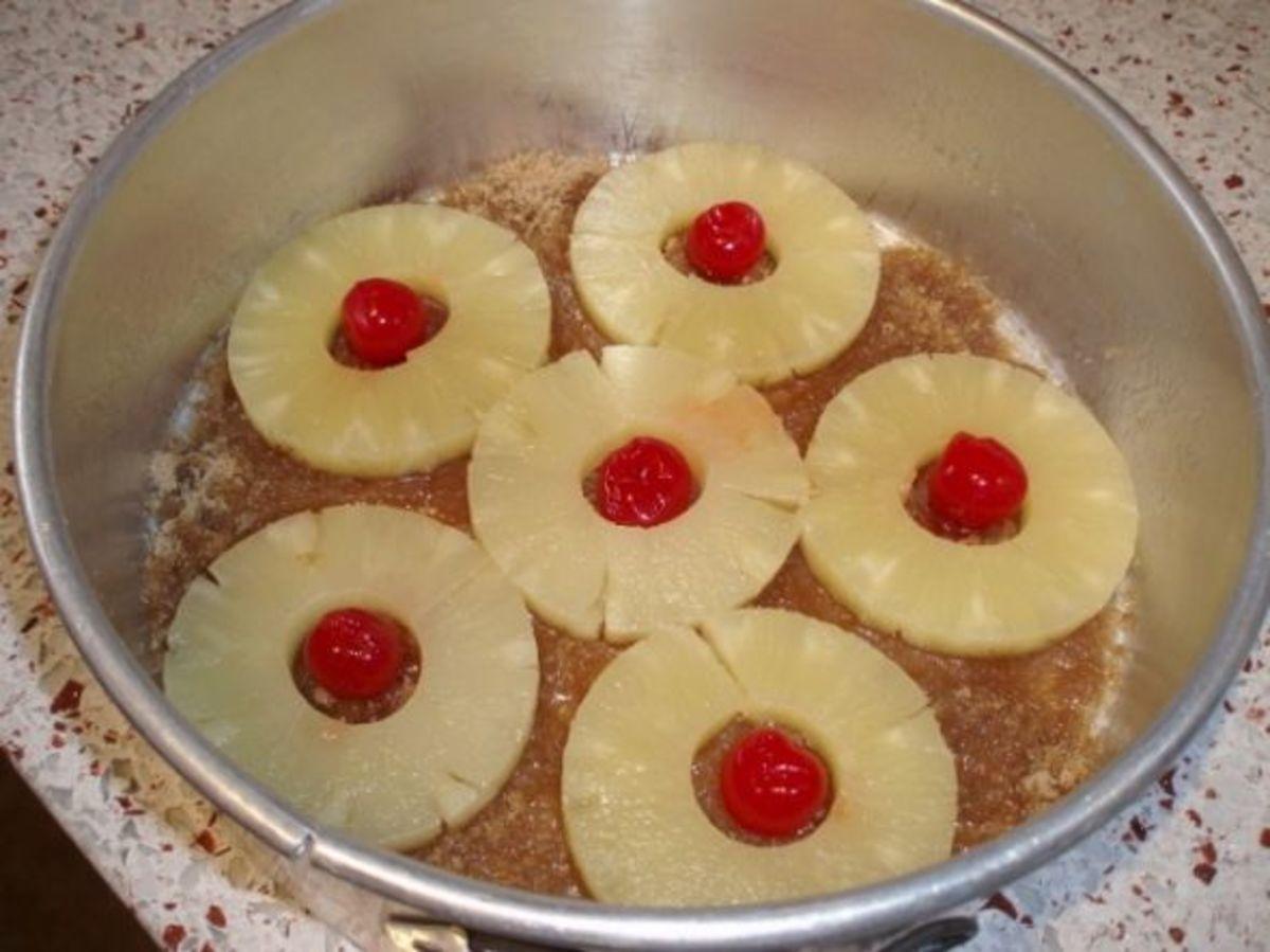 Pineapple rings and maraschino cherries on top of the brown sugar