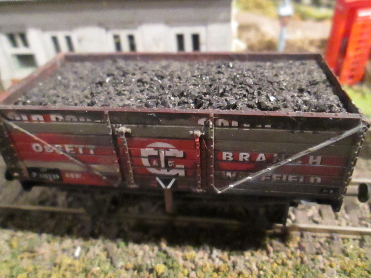 A Dapol private owner wagon, weathered and several planks scraped clean of the original paintwork (to resemble replaced planks) with Modelmaster wagon number transfers  The 'v' on the side indicates bottom doors for unloading into coal drop cells