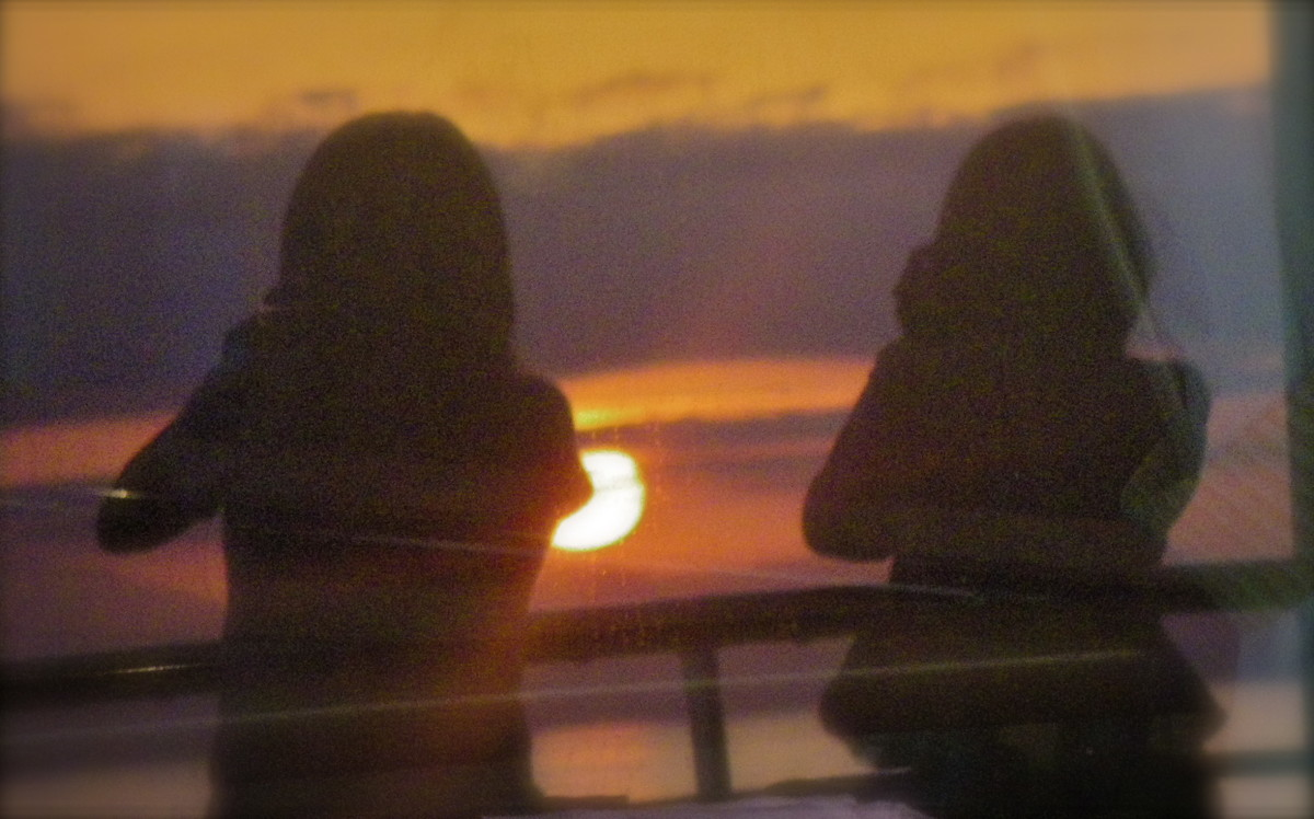 Two women shooting the sunset with their telephoto lenses as the Prinsendam sails in late afternoon.