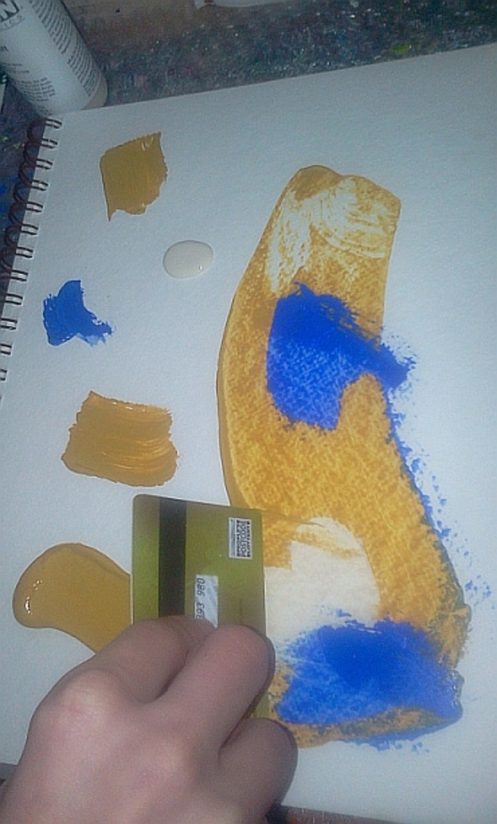 Moving acrylic paint around the page with an old credit card