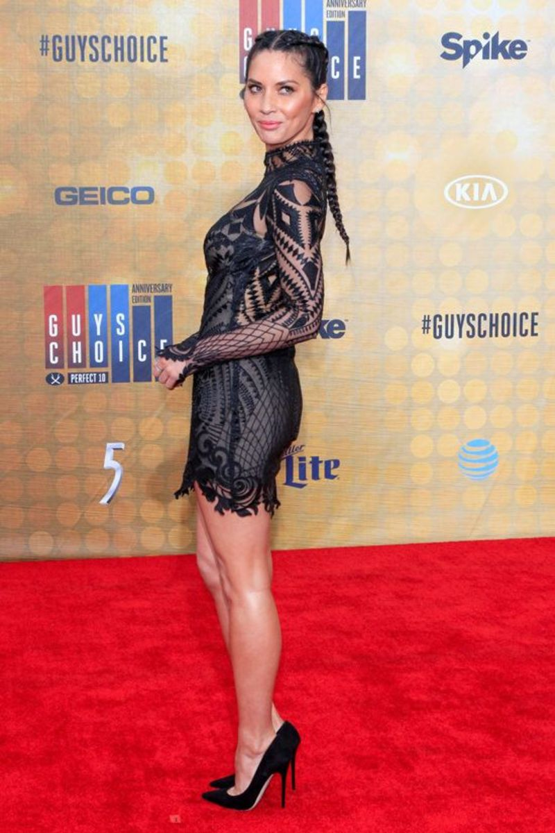 Olivia Munn in a black see through mini dress and sky high heels on the red carpet