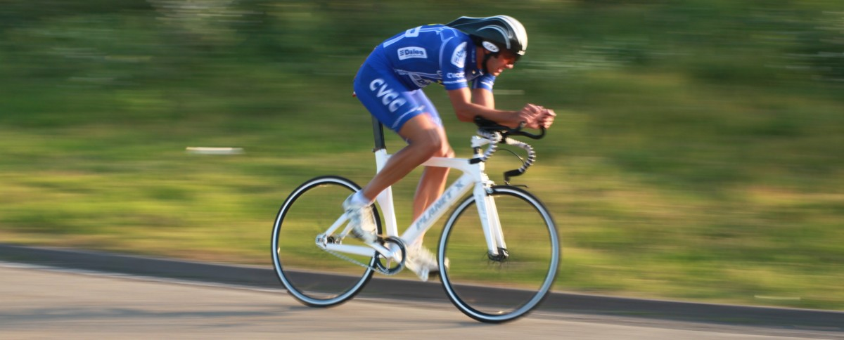 A rider aboard a fixed wheel time trial bike- a Planet X Carbon Track bike which has been adapted with tri-bars and brakes for legal road use