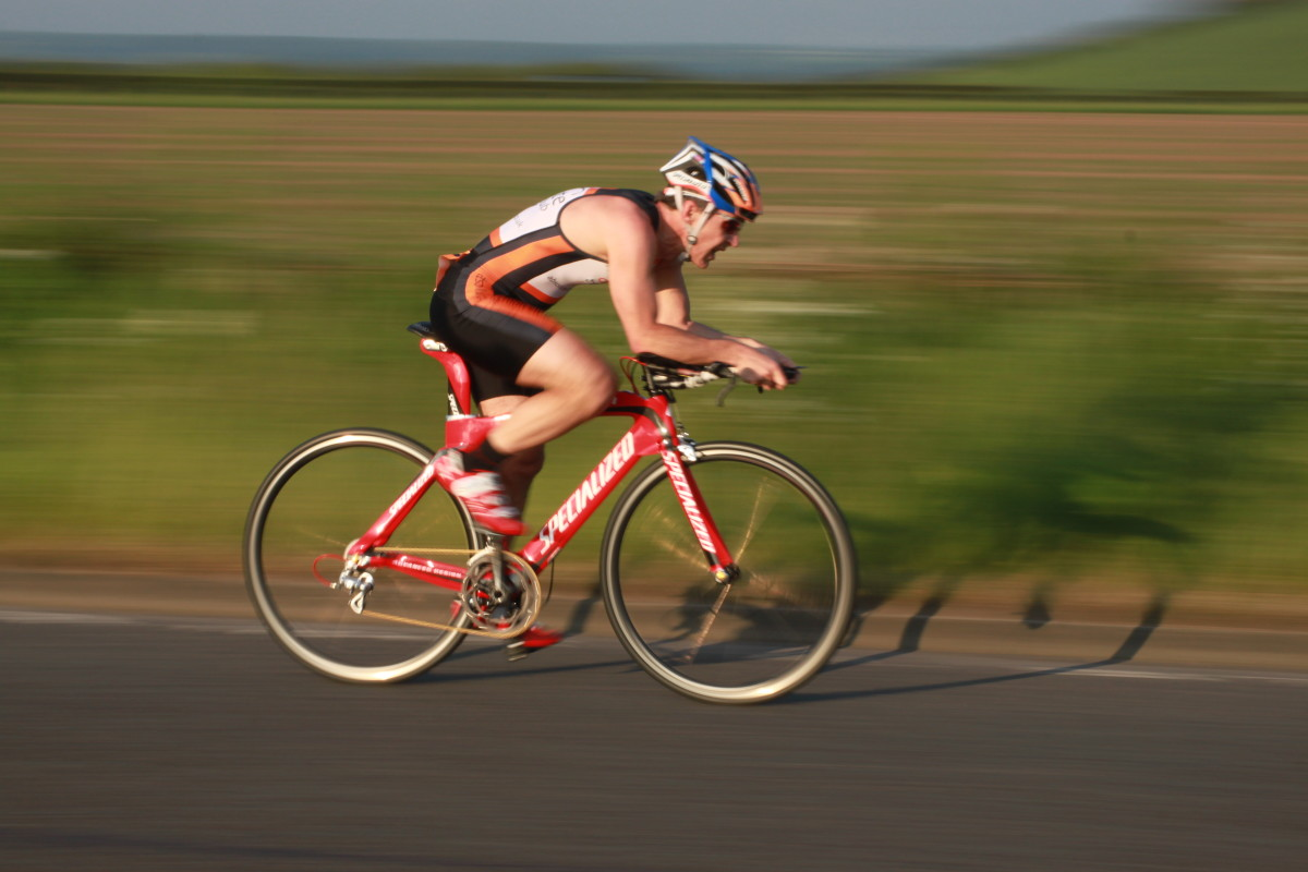A triathlete on a Specialised Time Trial Bike looking fast in a panning image