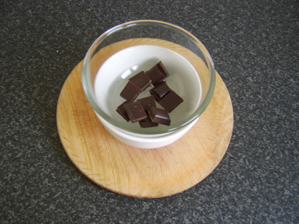 Chocolate is melted in one bowl over another bowl of hot water