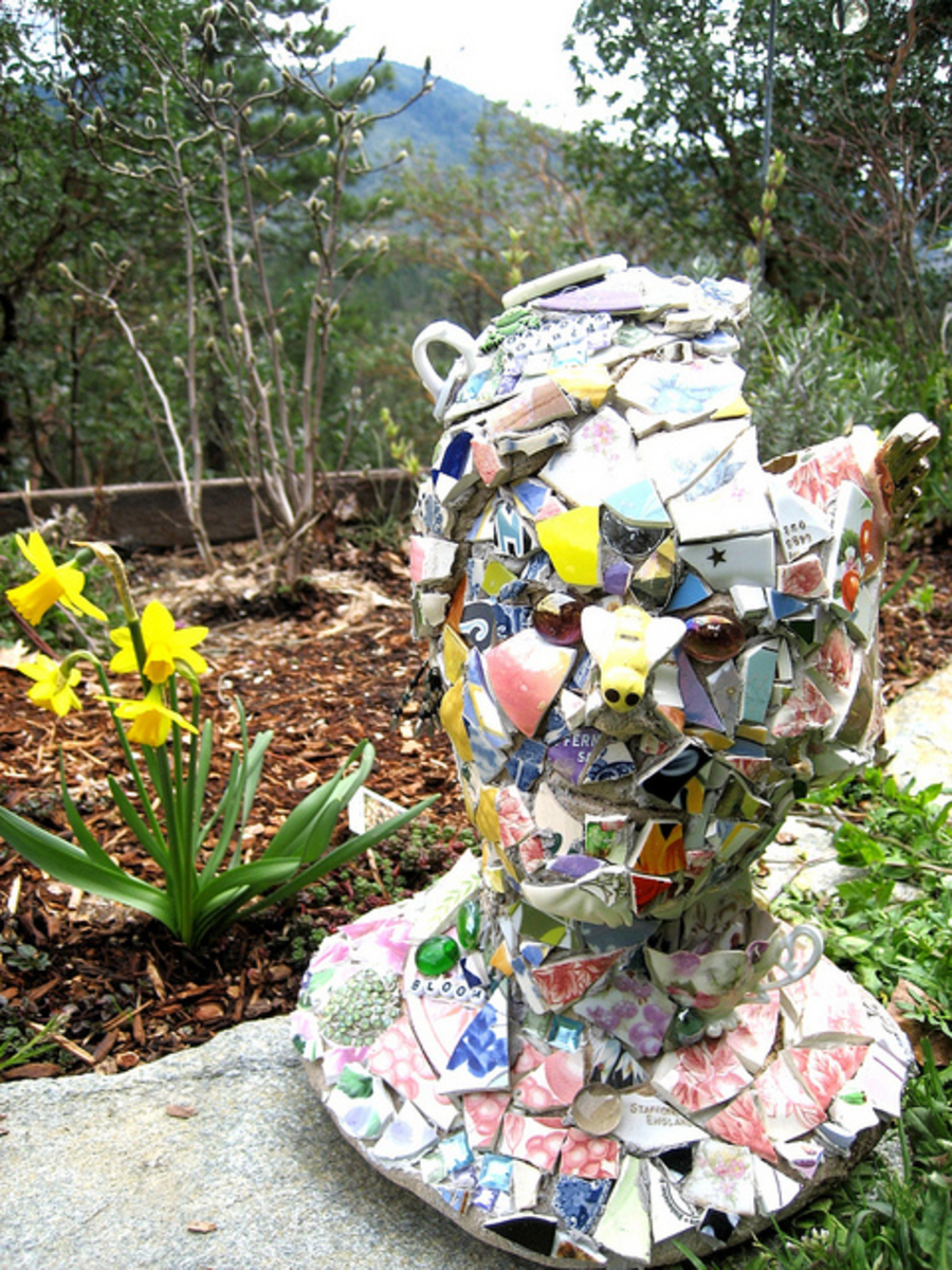 This mosaic garden sculpture has a base of cement and is then covered with lots of pieces of old vintage plates, china tea cups and assorted colored glass - and plenty of adhesive and grout.