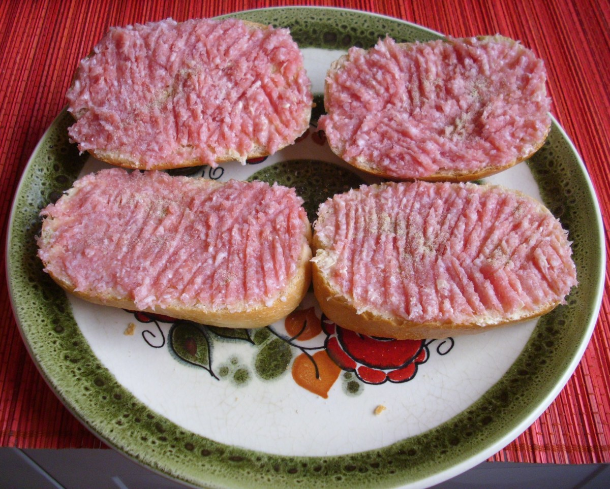 Half bread rolls with raw minced pork with salt and pepper.