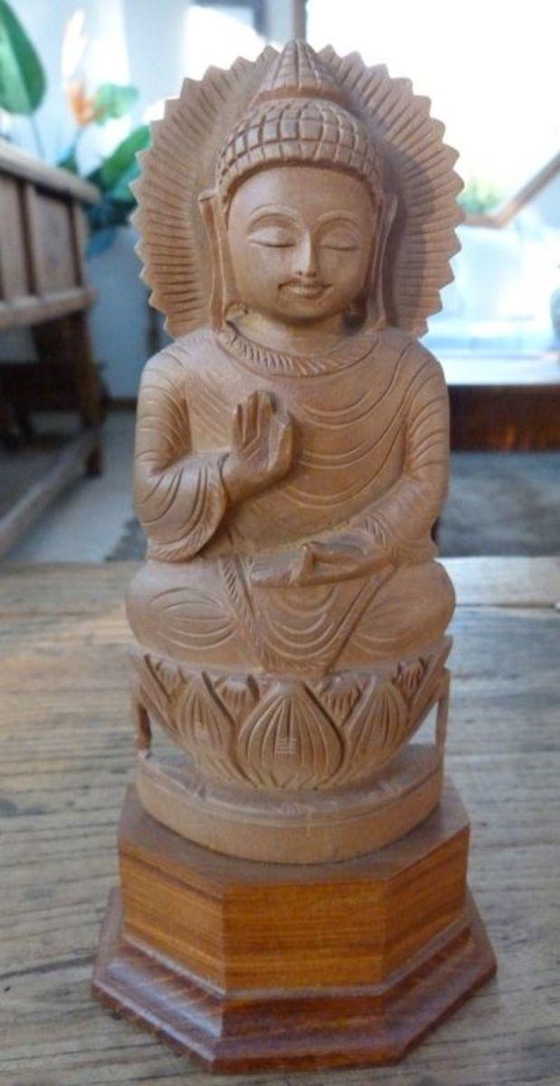 A Vitarka Mudra buddha carved out of sandalwood sitting on a lotus flower
