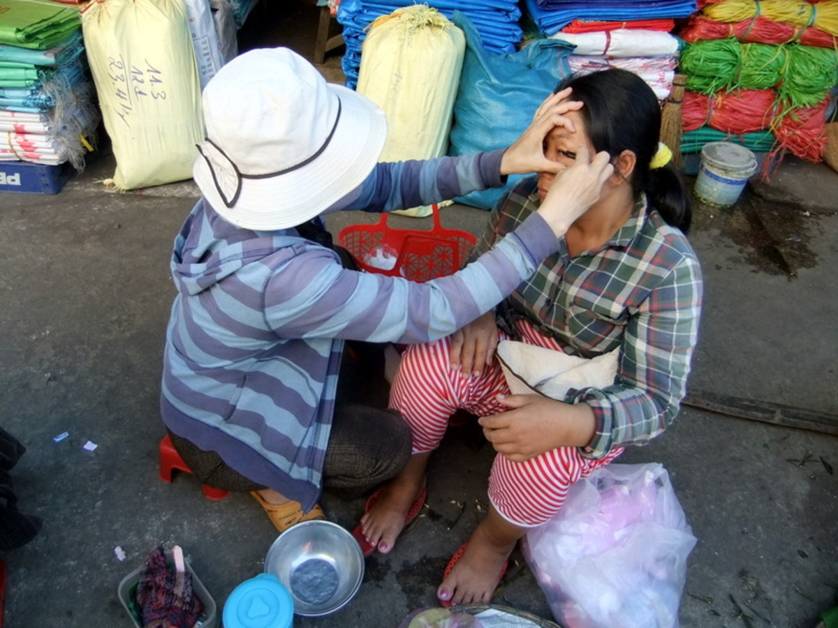 My travel to Vietnam: This woman was helping to trim her friend's eyebrow, while waiting for people to buy the plastic products at Dong Ba market in Hue. Looking pretty is still important in any part of the world.