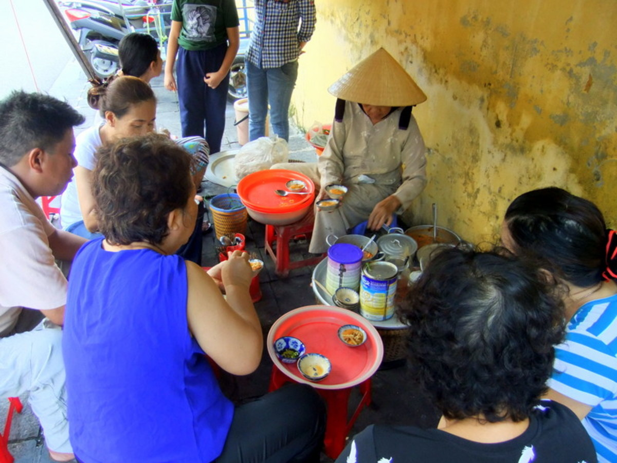 Street Photo in Hue, Vietnam: Enjoying the local fare from this street vendor in Hue, common street scenes here