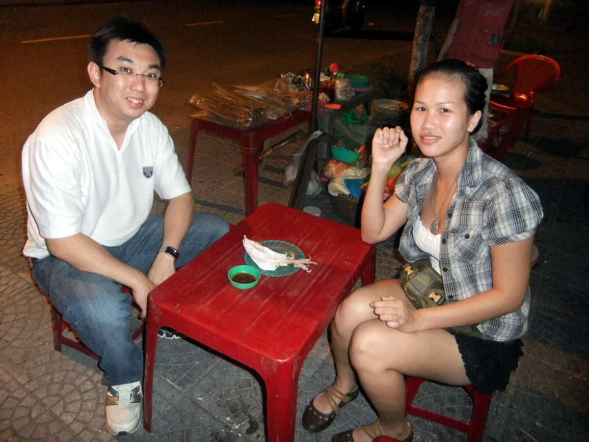 Street Photo in Hue, Vietnam: My friends trying out the roasted cuttlefish in Hue