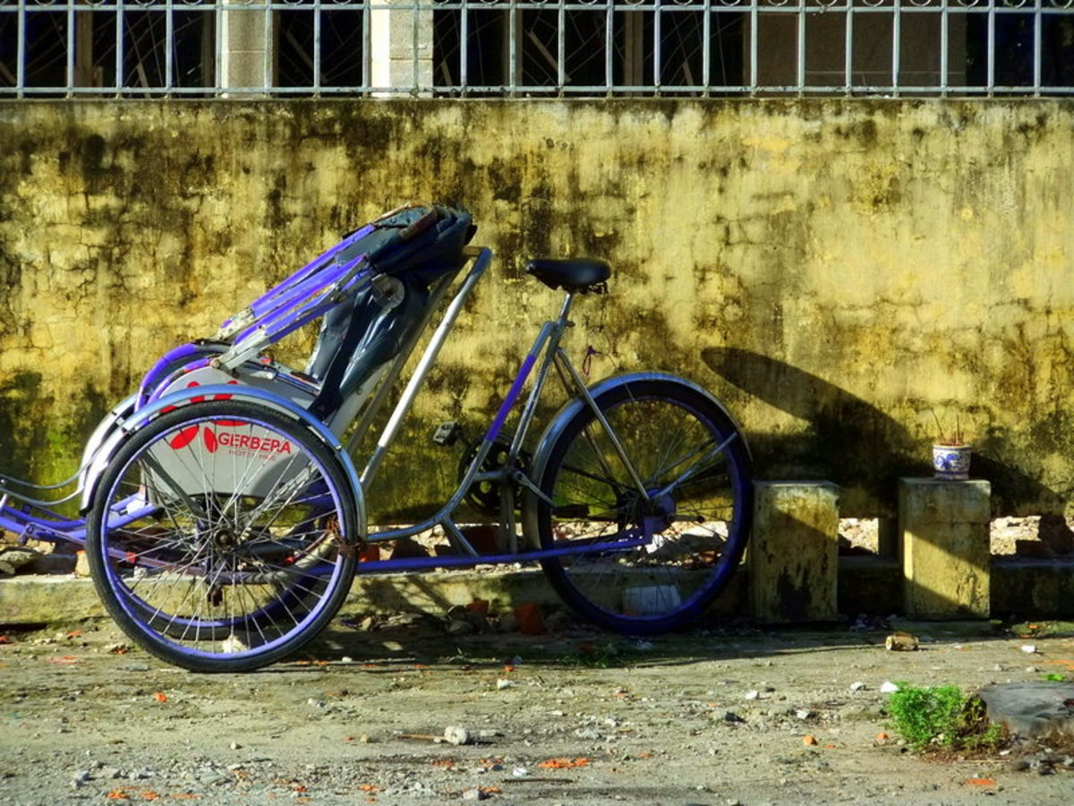 Street Photo in Hue, Vietnam: Cyclo or bicycle rickshaw, parked by the road kerb.